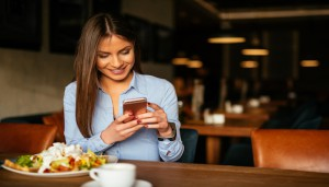 Woman holding a mobile phone and enjoying a breakfast.