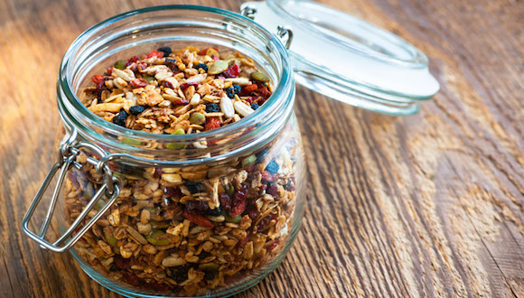 DYPC4N Homemade granola in open glass jar on rustic wooden background